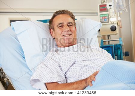 Portrait Of Male Patient Relaxing In Hospital Bed