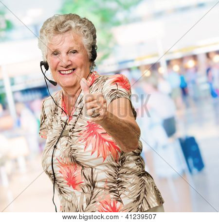 Senior Woman With Headset Showing Thumb-up Sign, Outdoors