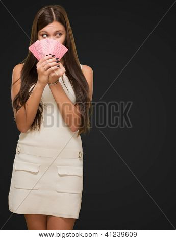 Pretty Young Woman Holding Playing Cards against a black background