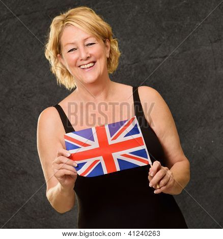 Happy Mature Woman Holding British Flag On Wall