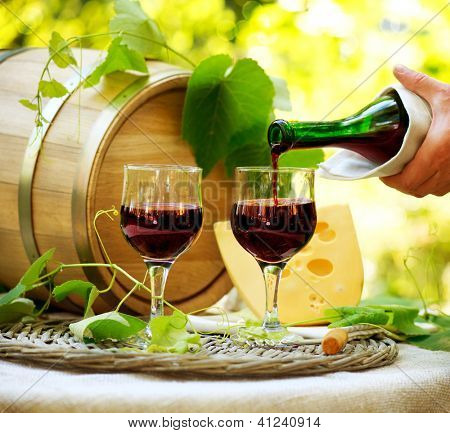 Wine. Red Wine and Cheese. Romantic Lunch Outdoor. Pouring Wine close-up. Outdoors