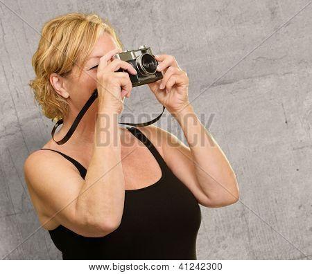 Mature Woman Looking Through Camera On Wall