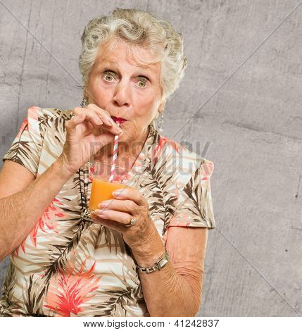 Woman Sipping Juice Through Straw On Wall