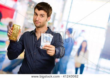 Joven hombre herraje de oro y monedas de Euro, en el interior
