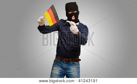 Man wearing a robber mask and holding airplane miniature and flag on grey background