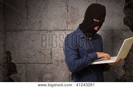 young male thief holding laptop on wall