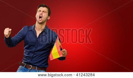 Man cheering and holding flag on red background