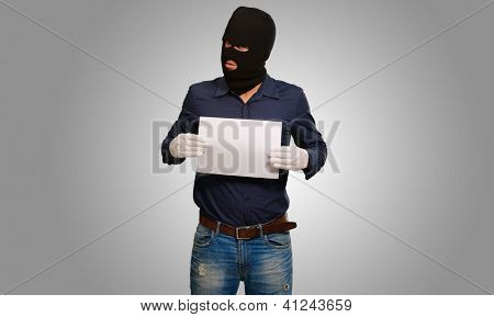 Man wearing a robber mask showing a blank paper on grey background