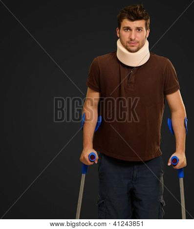 Man Walking On Crutches With Neck Brace Isolated On Black Background