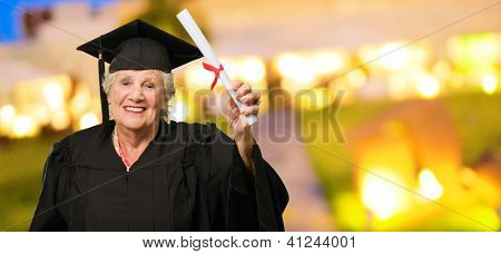 Senior Woman Holding Graduation Certificate, Outdoors