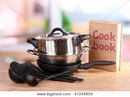 composition of kitchen tools and cook book on table in kitchen
