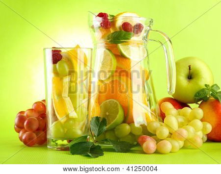 jar and glass with citrus fruits and raspberries, on green background