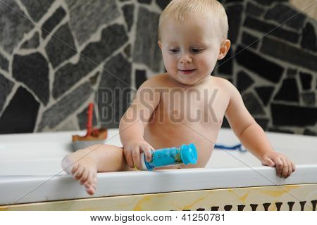 little baby boy taking a bath playing