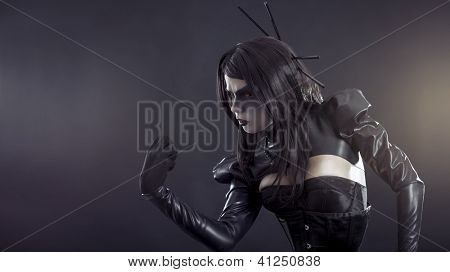 Angry witch with yellow eyes wearing black latex clothes