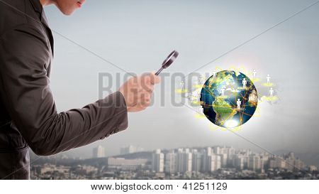 Homem de negócios olhar pequeno mundo sob uma lupa (elementos da imagem fornecida pela NASA)