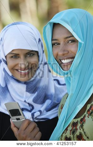 Portrait of two Asian female friends in headscarf holding mobile phone