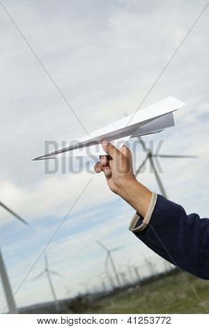 Close up of a little boy's hand holding paper plane in front of the wind turbine