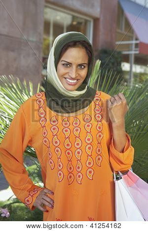 Portrait of a happy middle aged Indian female with shopping bags