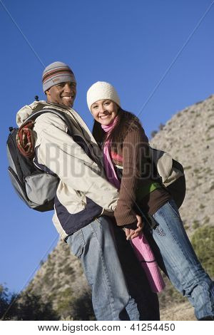Portrait of a multiethnic couple standing together while hiking