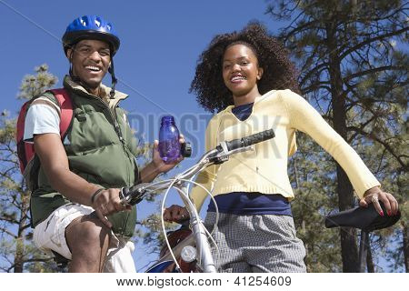 Portrait of a happy African American couple with bicycle