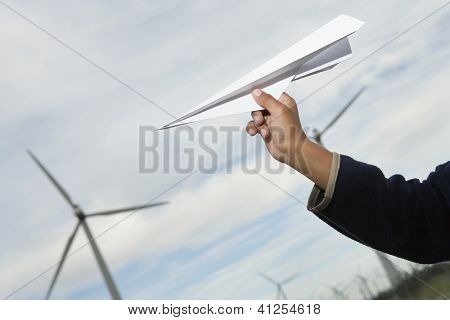 Little boy's hand holding paper plane in front of the wind turbine