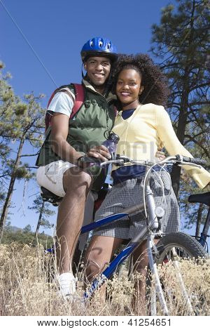 Low angle view of happy African American couple standing together with bicycle