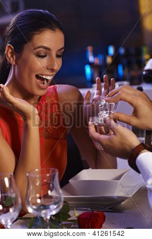 Young woman shouting with hapiness when man handing over engagement ring.