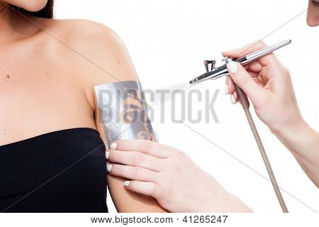 Spraying non-permanent tattoo on an arm