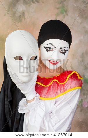 Smiling pierrot holding a sad white mask