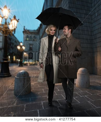Elegant couple with umbrella outdoors on rainy evening