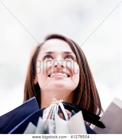 Pensive female shopper looking up holding shopping bags