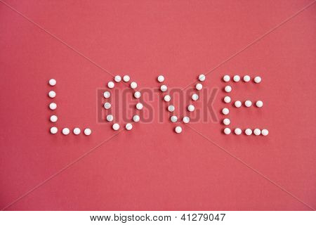 Close-up of push pins spelling love over colored background