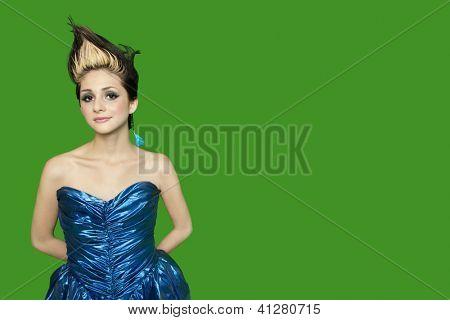 Portrait of spiked hair young woman with hands behind back over green background