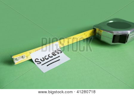 Close-up of sticky note stuck to measuring tape over colored background. Measure Success concept
