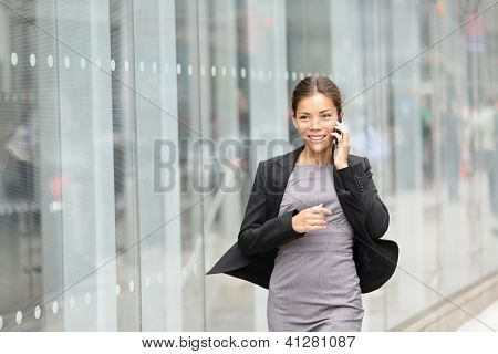 Business woman in motion, talking on mobile smart phone running outside on Manhattan, New York City. Beautiful young professional businesswoman. Multiethnic Asian Chinese and Caucasian ethnicity.