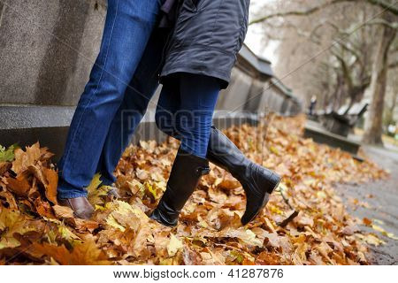 Detail of the legs of a couple kissing at the park in autumn