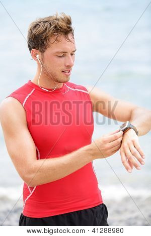 Running man looking at heart rate monitor GPS watch. Runner on beach listening to music in earphones wearing red compression t-shirt top.