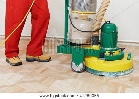 carpenter doing parquet Wood Floor polishing maintenance work by grinding machine