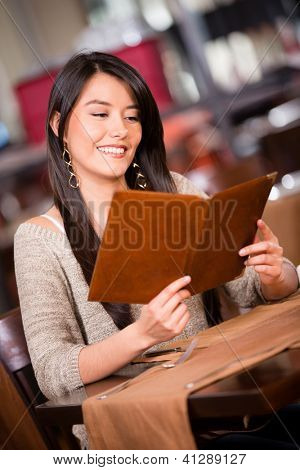 Beautiful woman looking at the menu in a restaurant
