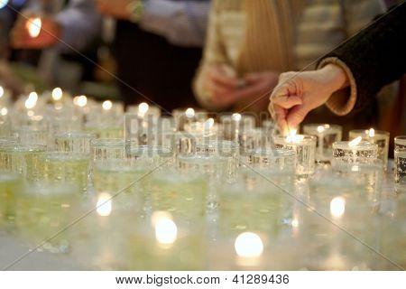 Hands lighting funeral candles