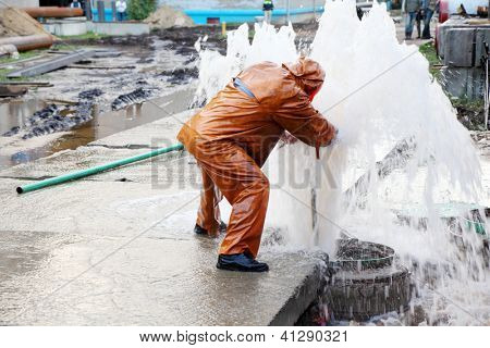 Worker in overalls eliminates breakthrough of sewerage systems.