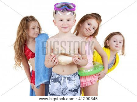 Four children in beach suits, boy stands in front, three girls  peek out from behind his back