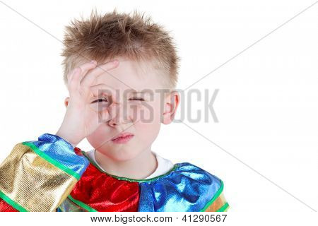 Little boy in carnival suit looks through ring made of thumb and forefinger of right hand