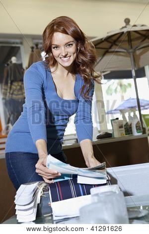Retrato de una joven feliz con muestras de textiles en tienda