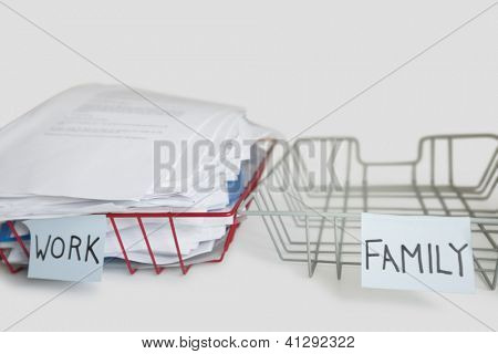 Pile of paperwork in work tray with empty family platter over white background