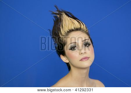 Portrait of beautiful young woman with spiked hair posing over blue background