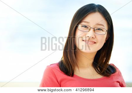 Portrait of happy girl in eyeglasses looking at camera with smile