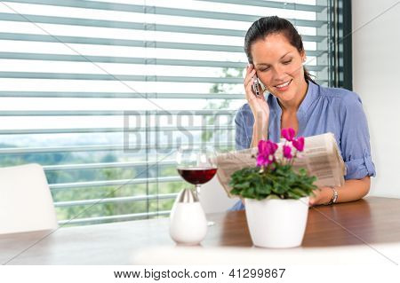 Smiling woman talking mobile phone relaxing reading home living room