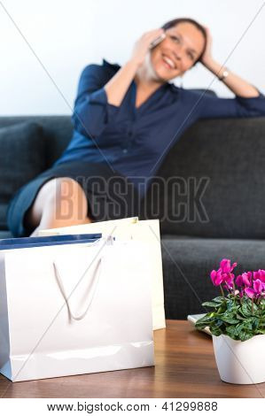 Smiling businesswoman talking cell phone bags home calling mobile