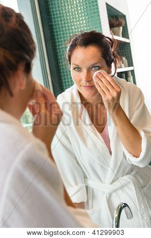 Young woman cleaning face cotton pads bathrobe bathroom morning preparation